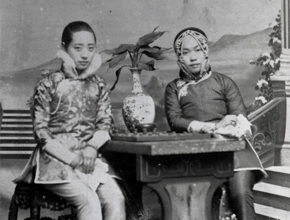 Amy Tan's grandmother (right) poses with a friend against a painted backdrop. Her outfit was an ensemble traditionally reserved for courtesans. Image courtesy Amy Tan