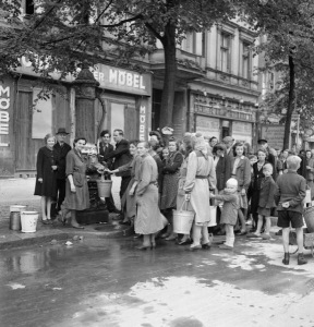 German civilians queue at a streetside water pump in Berlin; the only source of clean water after the destruction of the mains system by Allied bombs. RAF Flt Lt N.S. Clark/Imperial War Museum/Wikimedia Commons