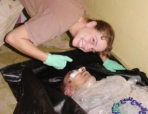 Specialist Sabrina Harman poses over the body of prisoner Manadel al-Jamadi, who was tortured to death during interrogation at Abu Ghraib. US Department of Defense/Wikimedia Commons