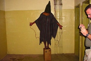 Iraqi prisoner Satar Jabar in Abu Ghraib, watched over by Staff Sergeant Ivan 'Chip' Frederick. US Department of Defense/Wikimedia Commons